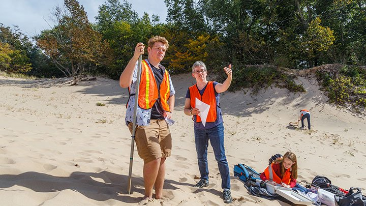 Professor Deanna Van Dijk and students doing research on a dune in P.J. Hoffmaster State Park.
